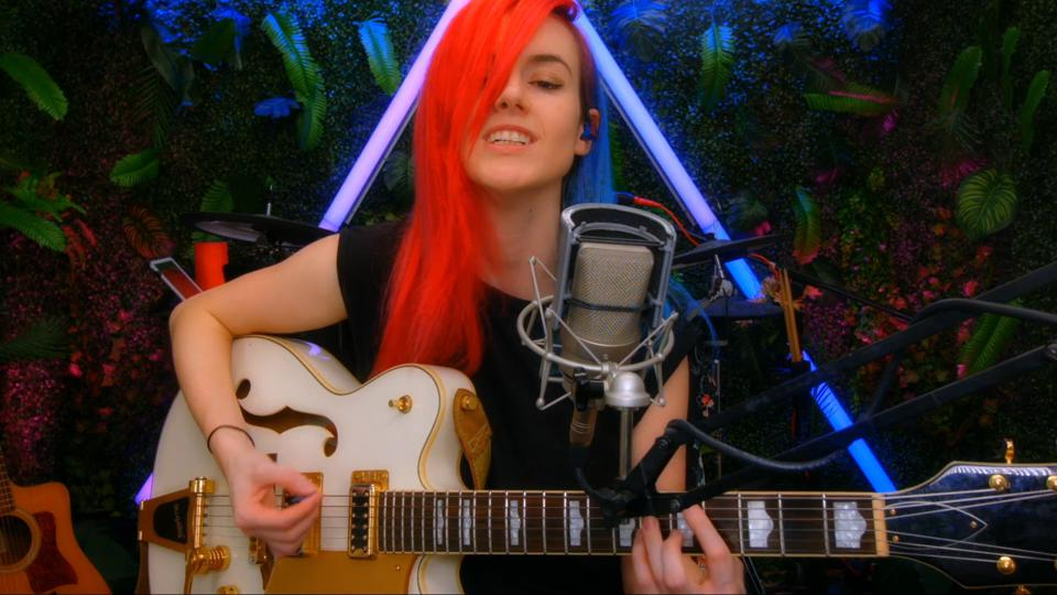 Emma McGann, a British singer, live streaming from her neon jungle home studio.