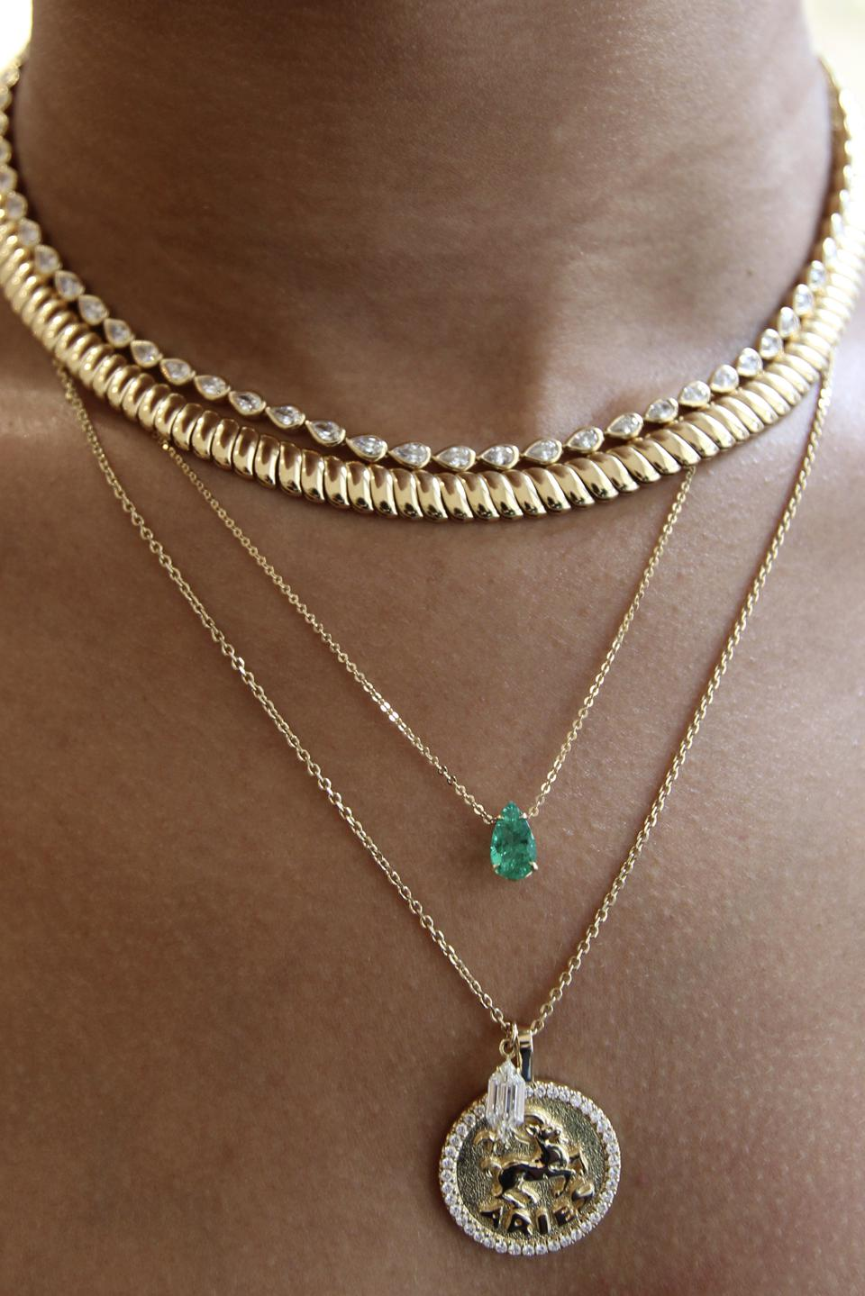A bare chest model wearing four various necklaces made from gold, diamonds or emerald.