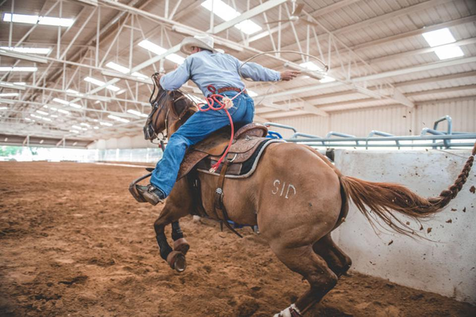 Tuf Cooper leaving the roping box on his horse at a run.