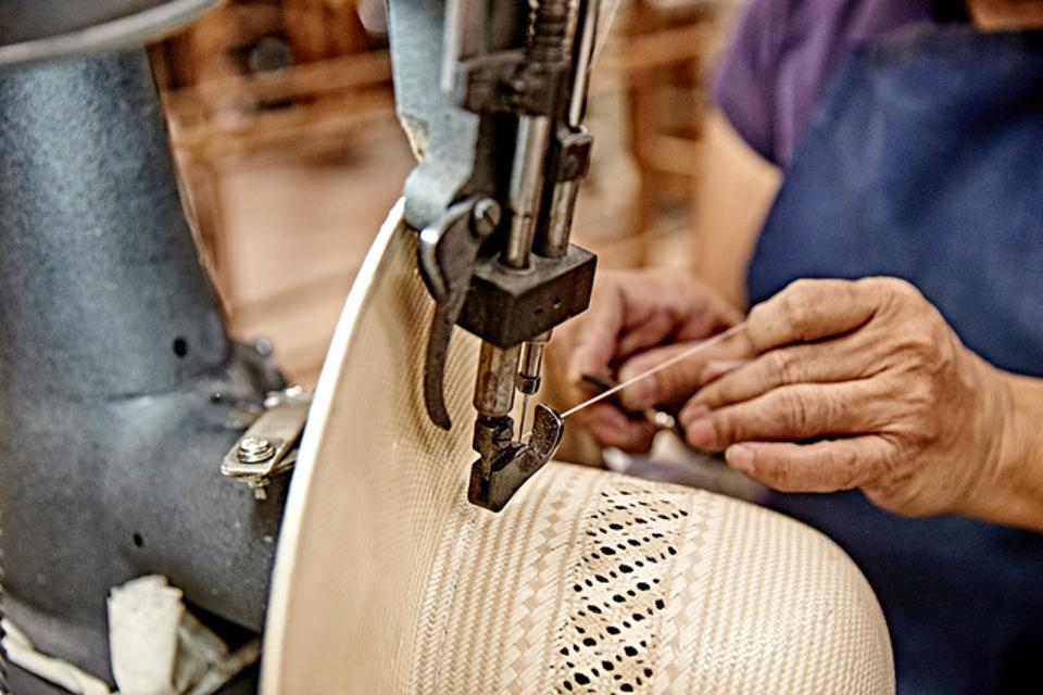 American straw hats are lacquered twice and pressed twice to provide unmatched durability and resistance to the elements. This straw hat is about to have the trim sewn on by hand.