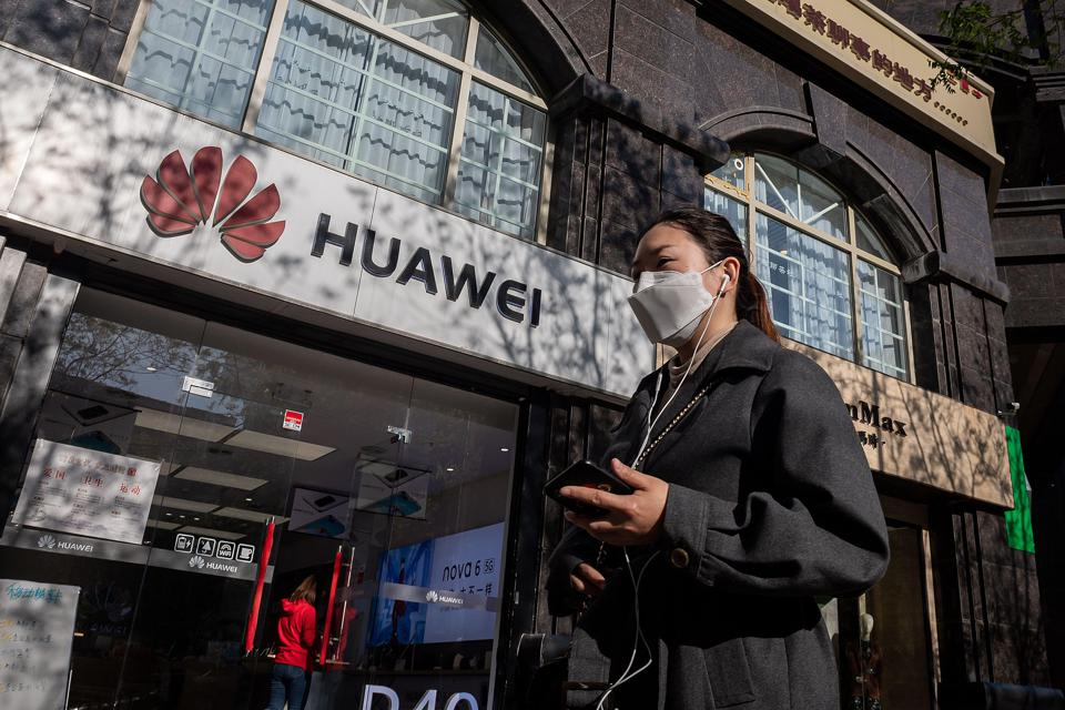 A woman with a smartphone walks past a Huawei shop.