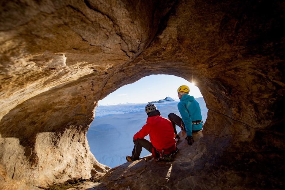 hikers on edge of cave looking at snowscape