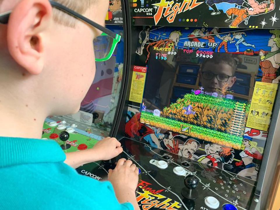 Boy plays built Arcade1Up machine