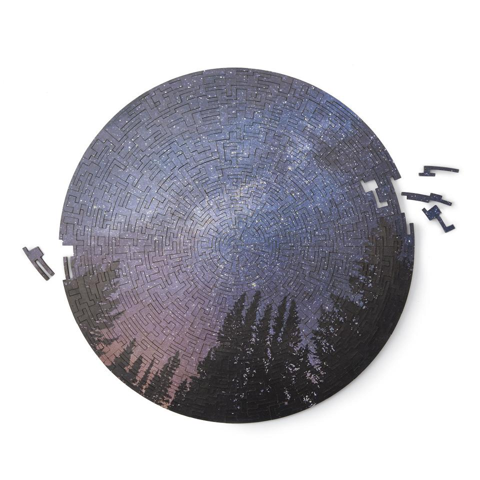 A round night sky puzzle showing stars and trees