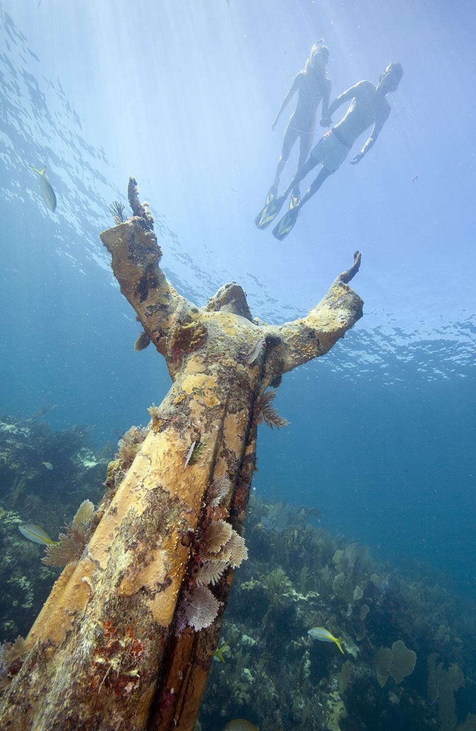 Snorkelers over the ″Christ of the Deep″ statue,in John Pennekamp Coral Reef State Park on Key Largo