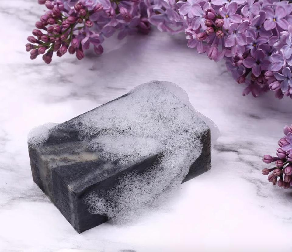 charcoal soap with suds and lavender flowers