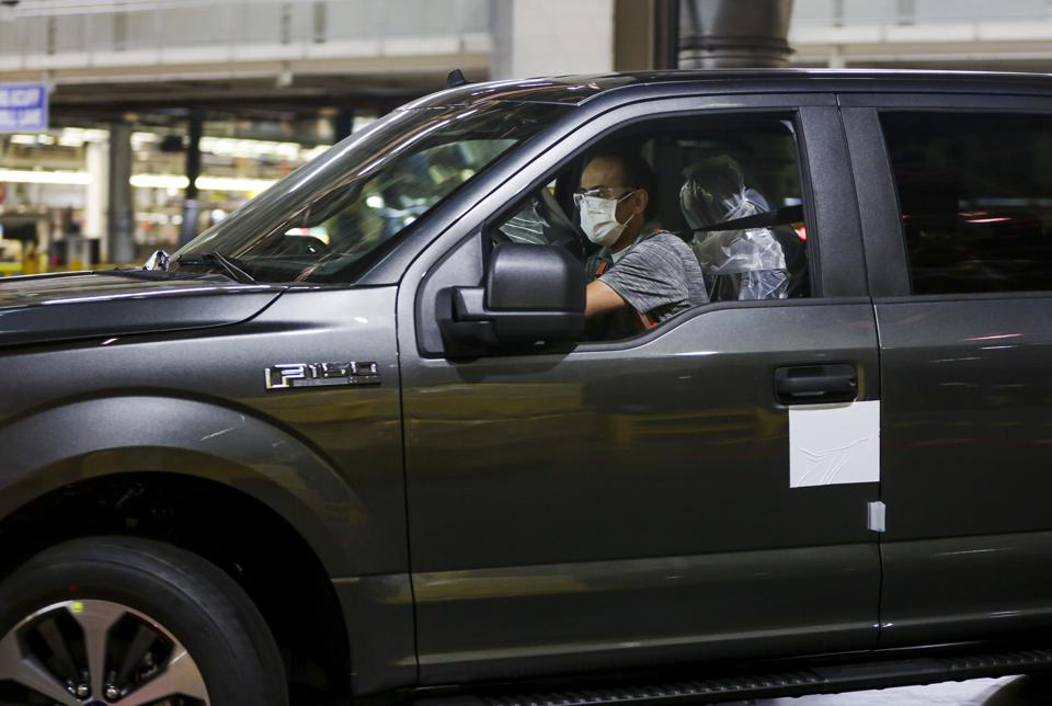 A worker wearing a face mask guides a Ford F150 pickup truck down an assembly line.
