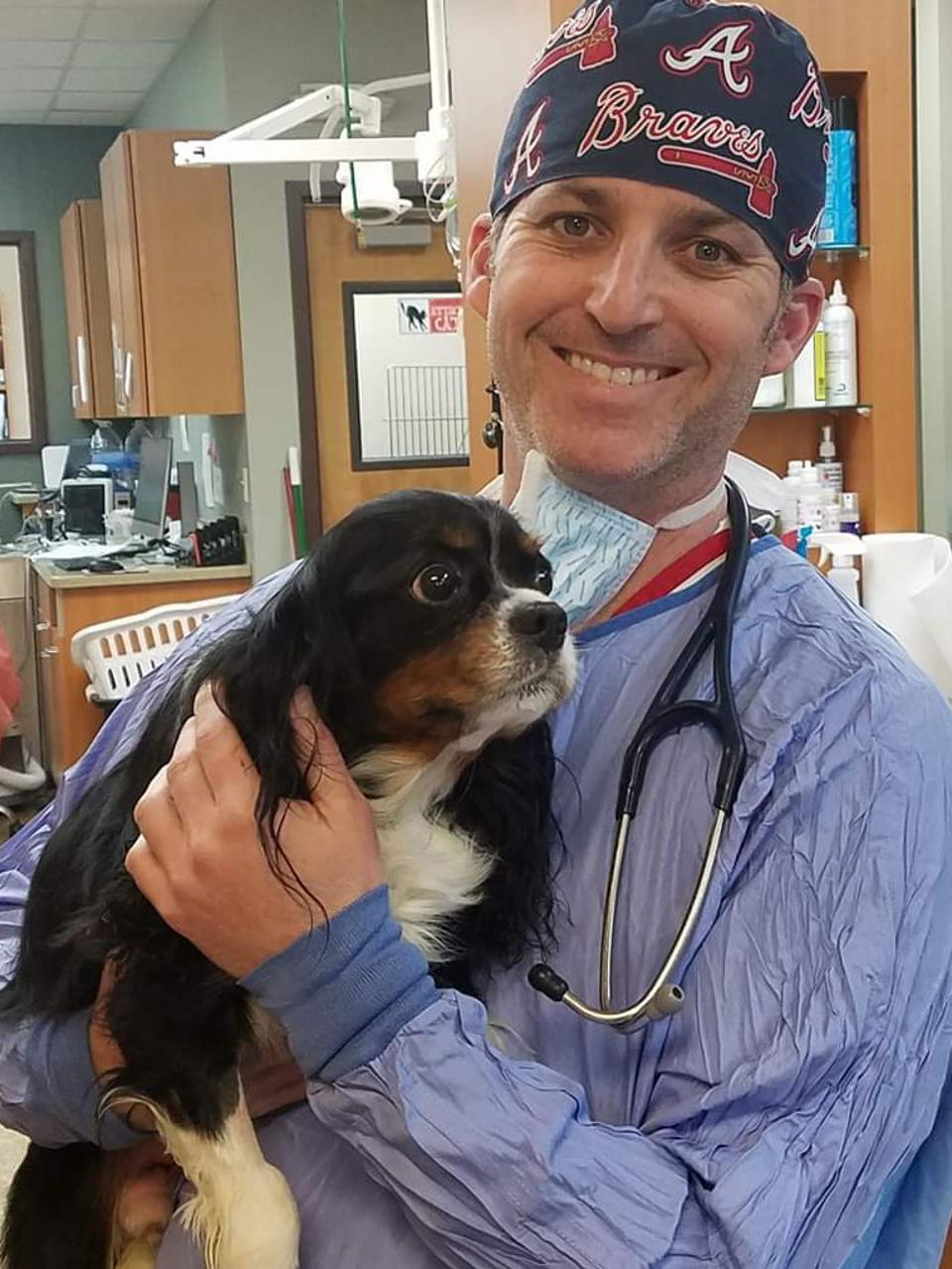 Veterinarian Jeff Bloomberg smiling while holding a dog patient.
