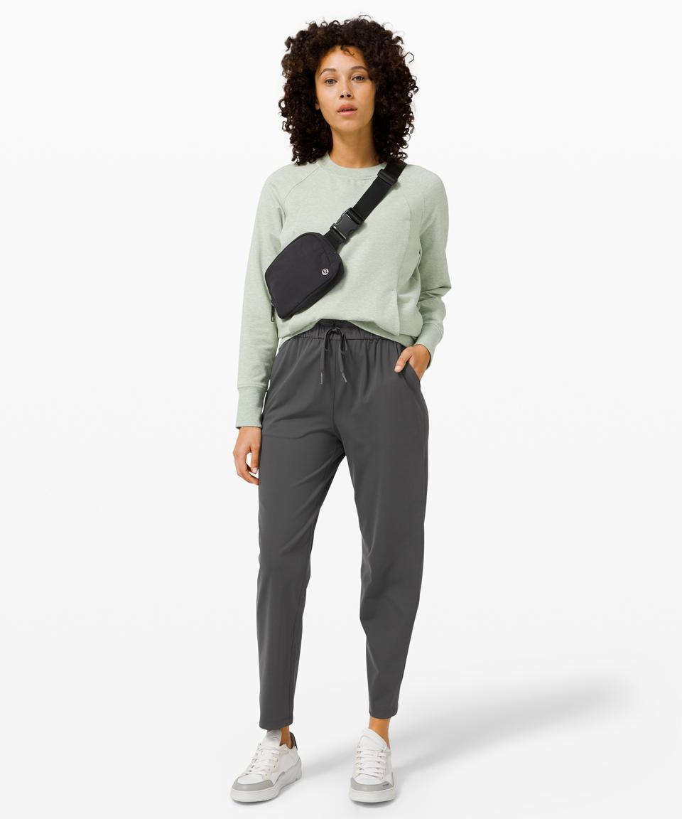 A model wearing grey keep moving pants by lululemon with a green top