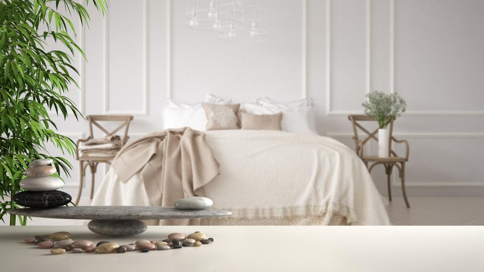 White table shelf with pebble balance and bamboo plant over vintage classic bedroom with soft bed full of pillows and blankets, zen concept interior design