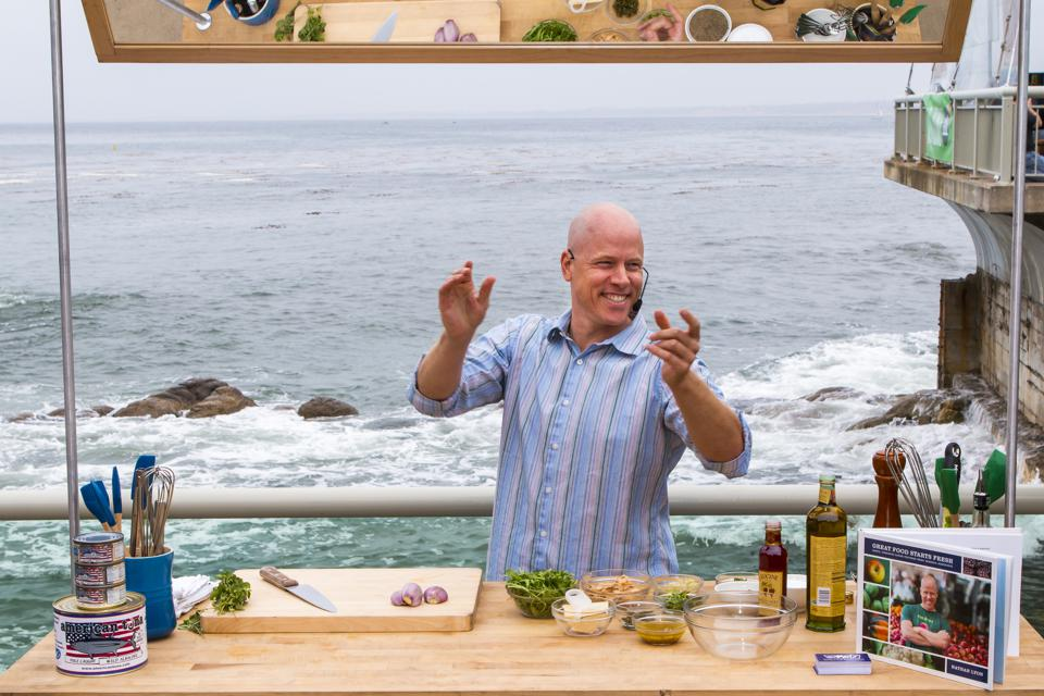 Chef Nathan Lyon doing a cooking demo at the Monterey Bay Aquarium's Cooking for Solutions event in front of the ocean.