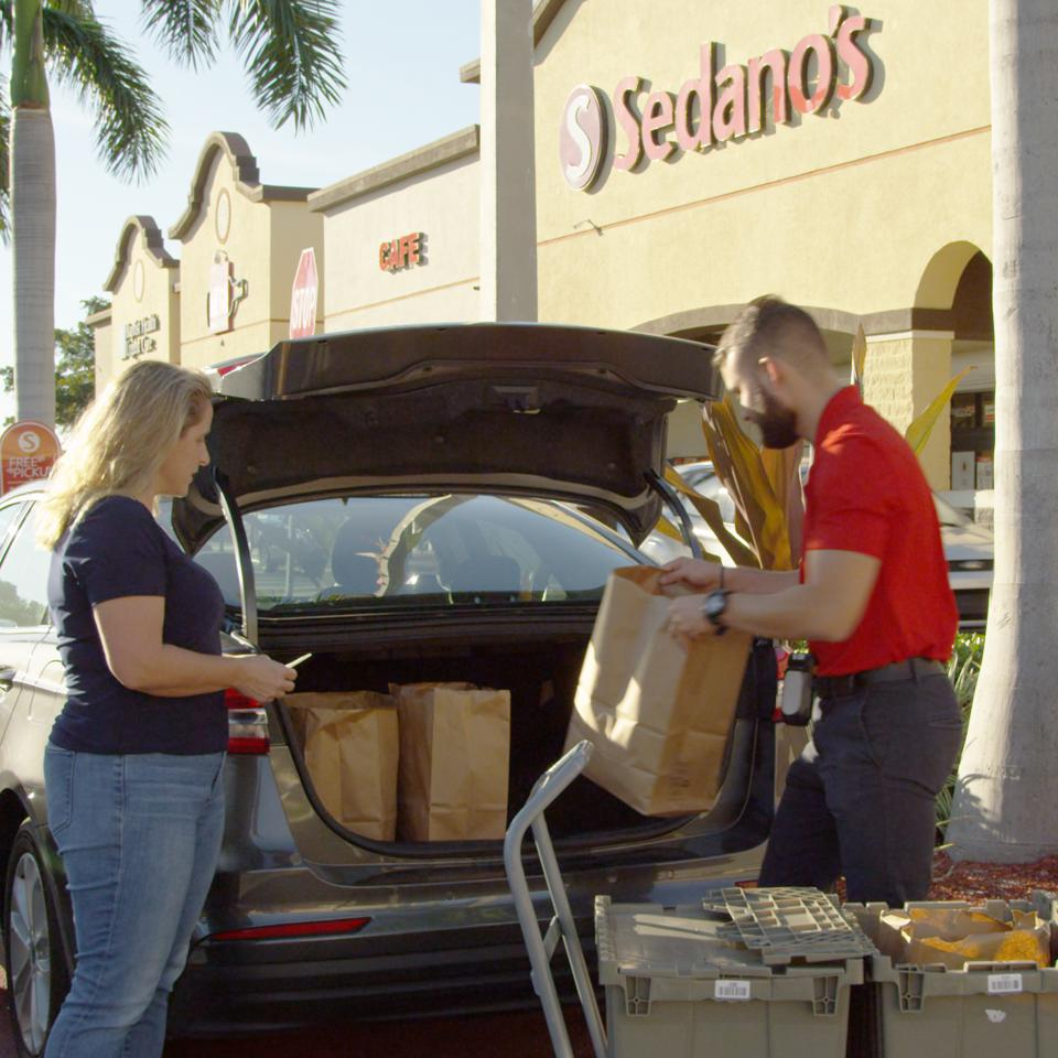A sales manager from a small supermarket chain, Sedano's, helps a customer load her groceries in her car.