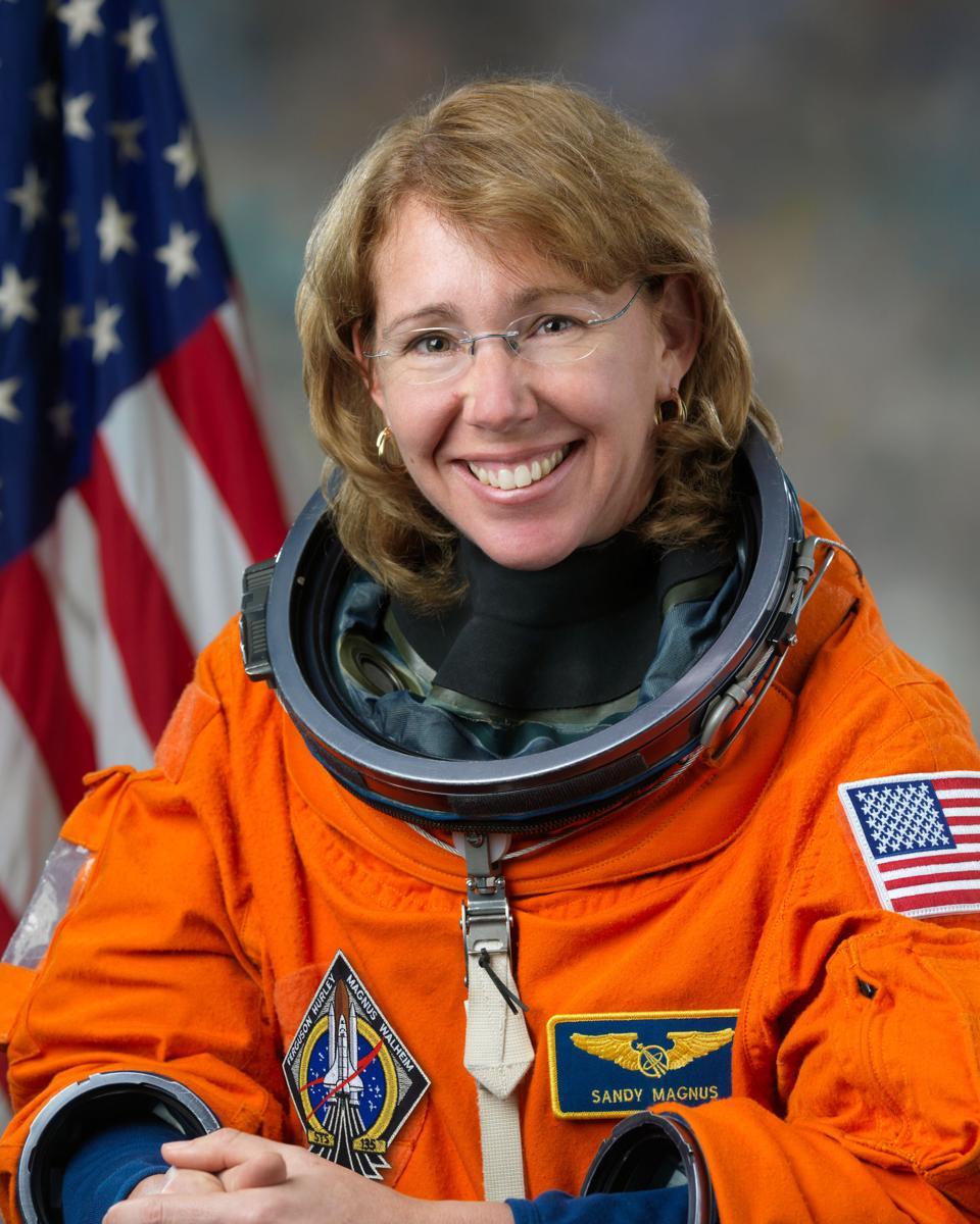 Astronaut Sandy Magnus in her orange flight suit
