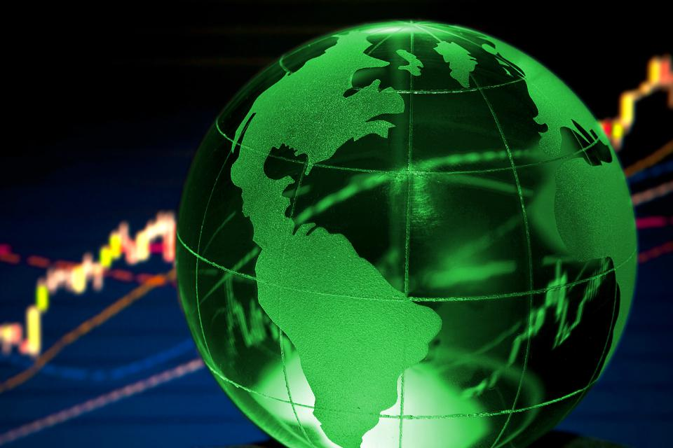 The green globe is spinning with backdrop of stock prices rising