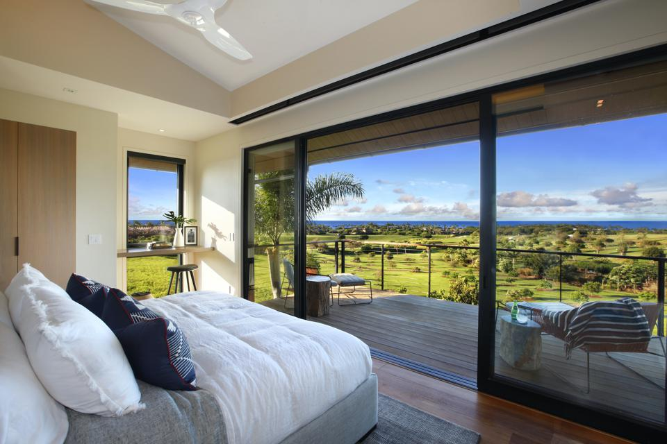 In the master bedroom, sliding glass doors open to a private lanai with a view of the ocean.