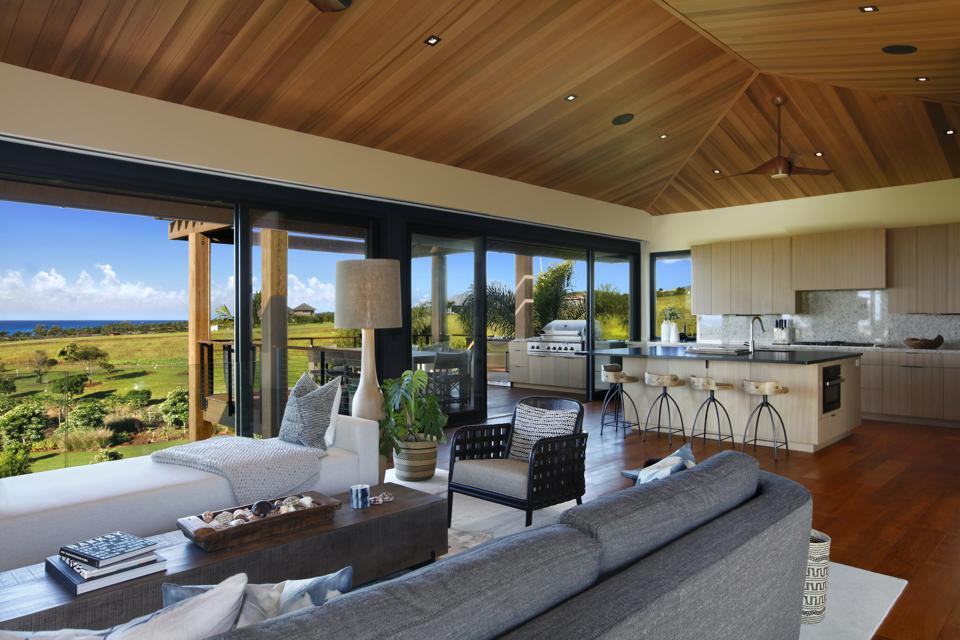 The home features a variety of gathering spaces with expansive doors and windows that open up to the outdoors. The great room and open kitchen are seen here.