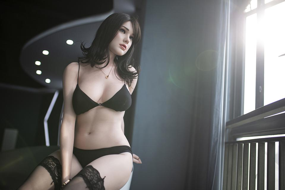 A sex doll dressed in black underwear is positioned next to a window