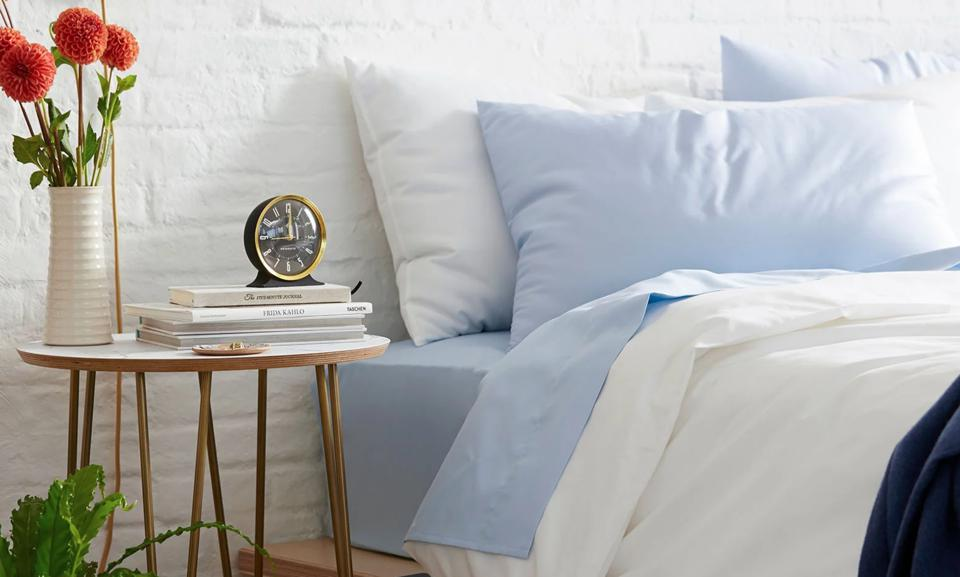 A bed made with blue sheets and a white duvet