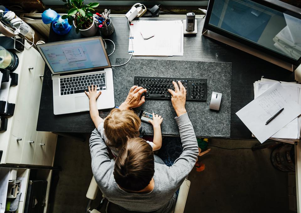 Aerial View Of Mother Working In Office At Home With Daughter