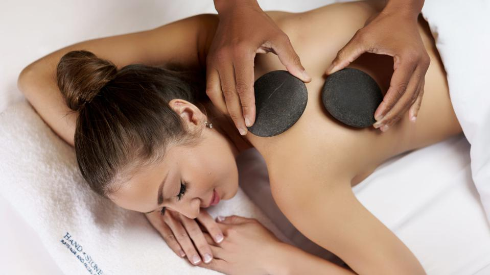 A woman getting a hot stone massage at a Hand & Stone spa.