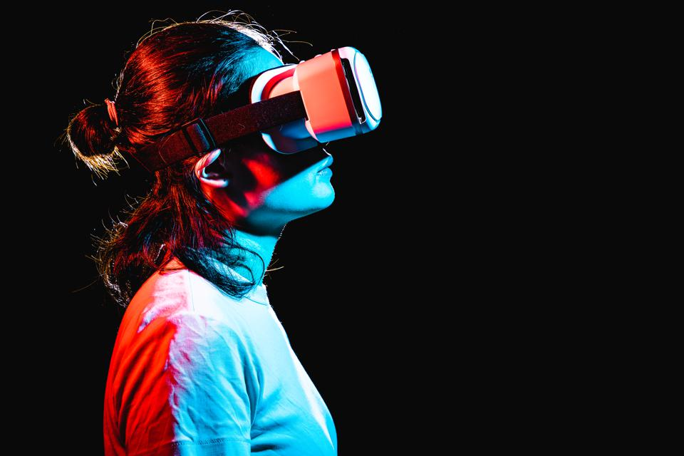 Woman using Virtual Reality headset at night
