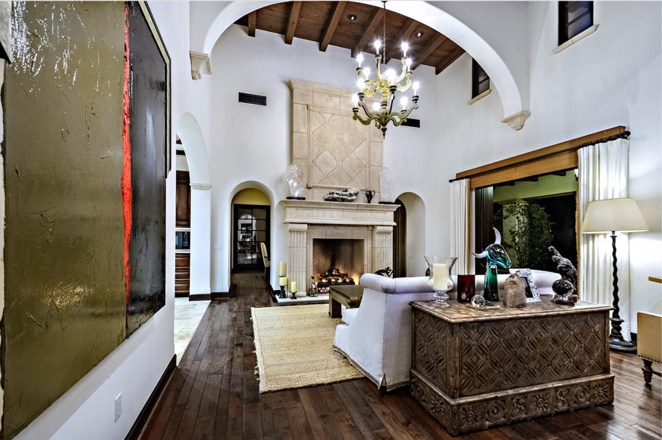 The living room has arched white stucco walls, wooden beams, chandeliers, and massive fireplace.