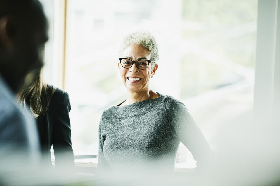 Portrait of smiling senior businesswoman in discussion with coworkers