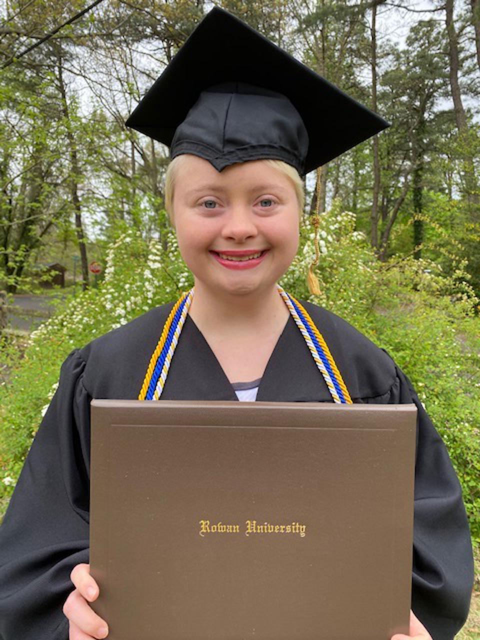 AnnaRose Rubright in her cap and gown holding her Rowan University diploma.