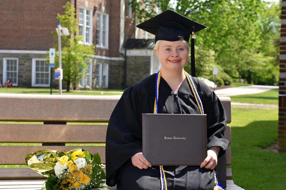 AnnaRose Rubright in her cap and gown, holding her diploma at Rowan University.
