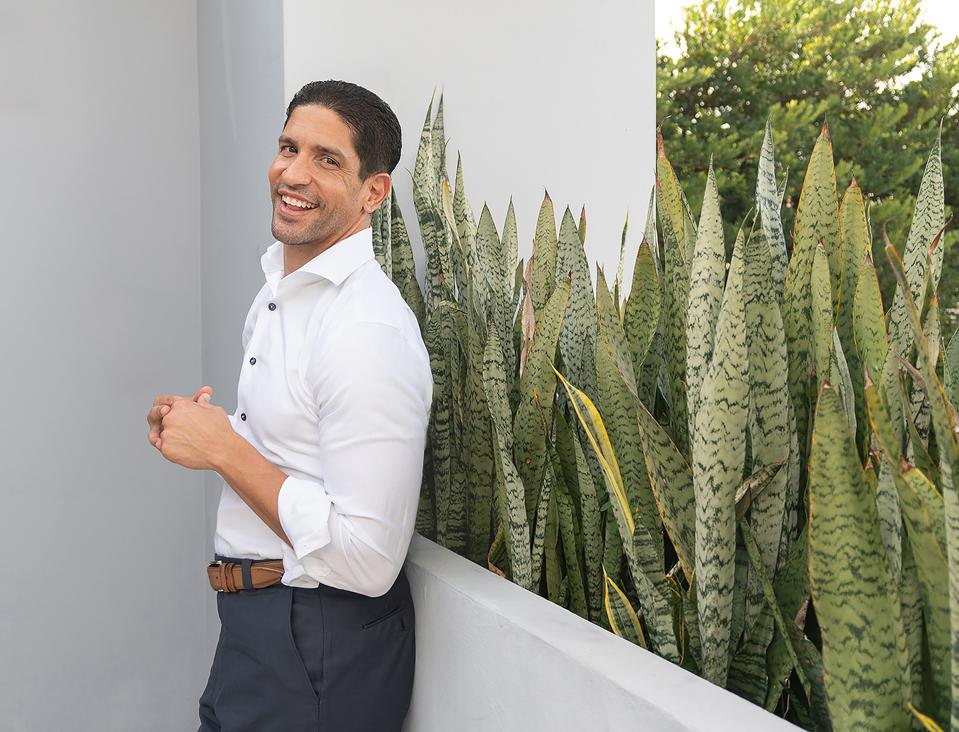man in white shirt standing against plants