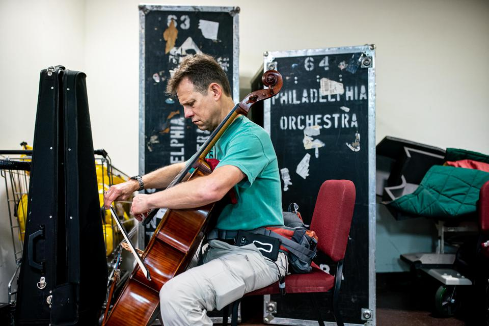 Cellist Robert Cafaro practices backstage amongst the Orchestra's luggage in Taipei.