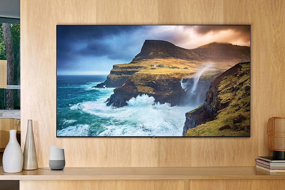 A wall-mounted flat screen television shows a beautiful, vivid landscape scene