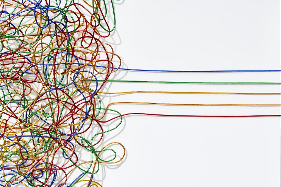 Jumble of multicoloured wires untangling into straight lines over a white background.