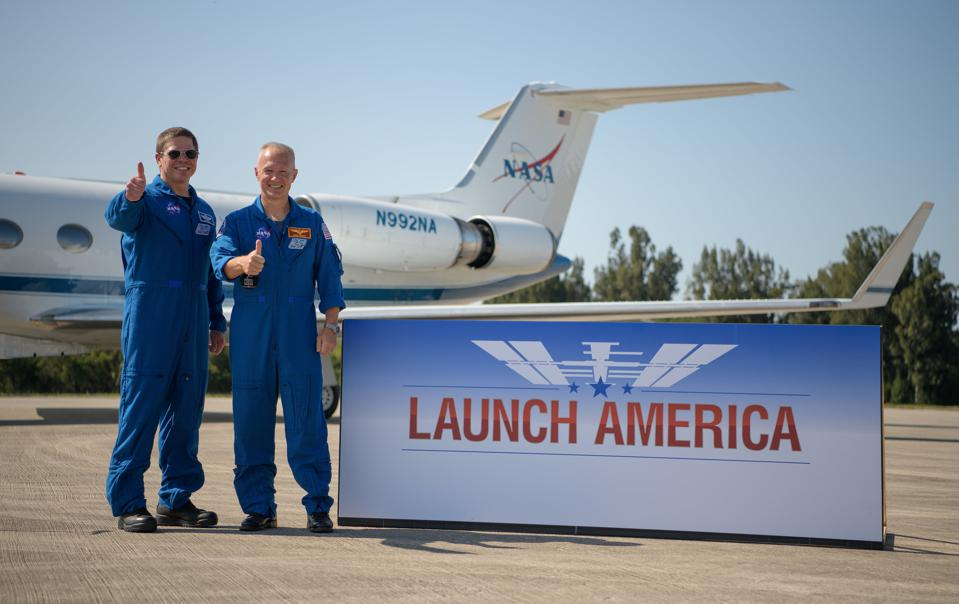 NASA astronauts Robert Behnken, left, and Douglas Hurley gives a thumbs up after arriving at the Launch and Landing Facility at NASA's Kennedy Space Center ahead of SpaceX's Demo-2 mission, Wednesday, May 20, 2020, in Florida. NASA's SpaceX Demo-2 mission is the first launch with astronauts of the SpaceX Crew Dragon spacecraft and Falcon 9 rocket to the International Space Station as part of the agency's Commercial Crew Program. The flight test will serve as an end-to-end demonstration of SpaceX's crew transportation system. Behnken and Hurley are scheduled to launch at 4:33 p.m. EDT on Wednesday, May 27, from Launch Complex 39A at the Kennedy Space Center. A new era of human spaceflight is set to begin as American astronauts once again launch on an American rocket from American soil to low-Earth orbit for the first time since the conclusion of the Space Shuttle Program in 2011. Photo Credit: (NASA/Bill Ingalls)