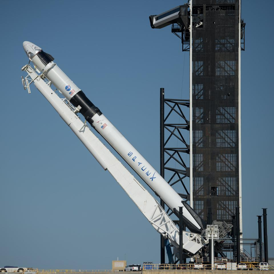 A SpaceX Falcon 9 rocket with the company's Crew Dragon spacecraft onboard is seen as it is raised into a vertical position on the launch pad at Launch Complex 39A as preparations continue for the Demo-2 mission, Thursday, May 21, 2020, at NASA's Kennedy Space Center in Florida. NASA's SpaceX Demo-2 mission is the first launch with astronauts of the SpaceX Crew Dragon spacecraft and Falcon 9 rocket to the International Space Station as part of the agency's Commercial Crew Program. The flight test will serve as an end-to-end demonstration of SpaceX's crew transportation system. Behnken and Hurley are scheduled to launch at 4:33 p.m. EDT on Wednesday, May 27, from Launch Complex 39A at the Kennedy Space Center. A new era of human spaceflight is set to begin as American astronauts once again launch on an American rocket from American soil to low-Earth orbit for the first time since the conclusion of the Space Shuttle Program in 2011. Photo Credit: (NASA/Bill Ingalls)