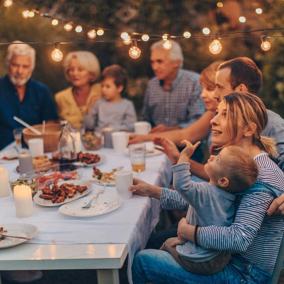 Outdoor String Lights, family at a table in the evening enjoying barbecue