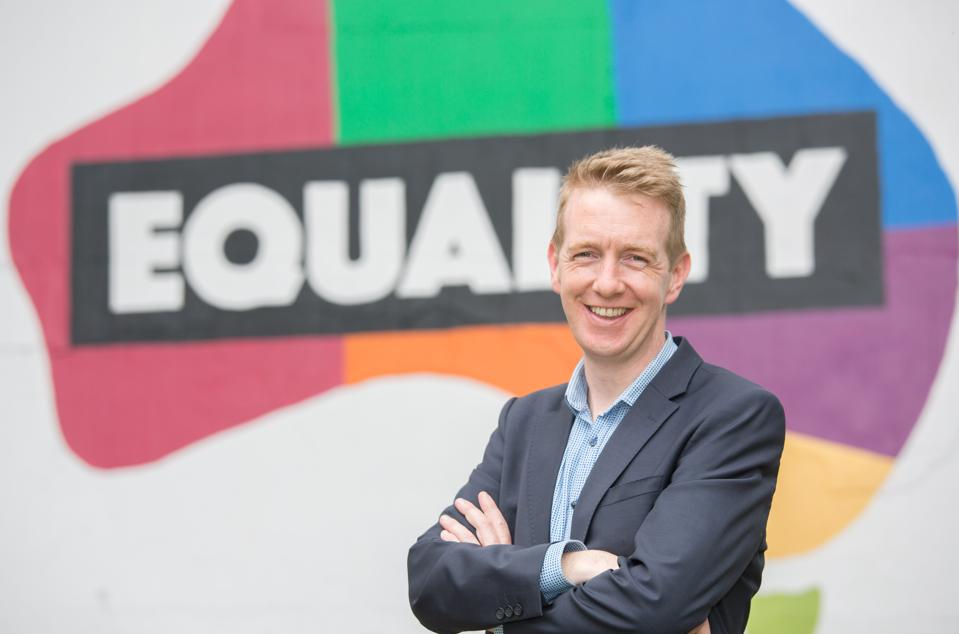 Brady stands in front of an Australian Equal Marriage campaign banner