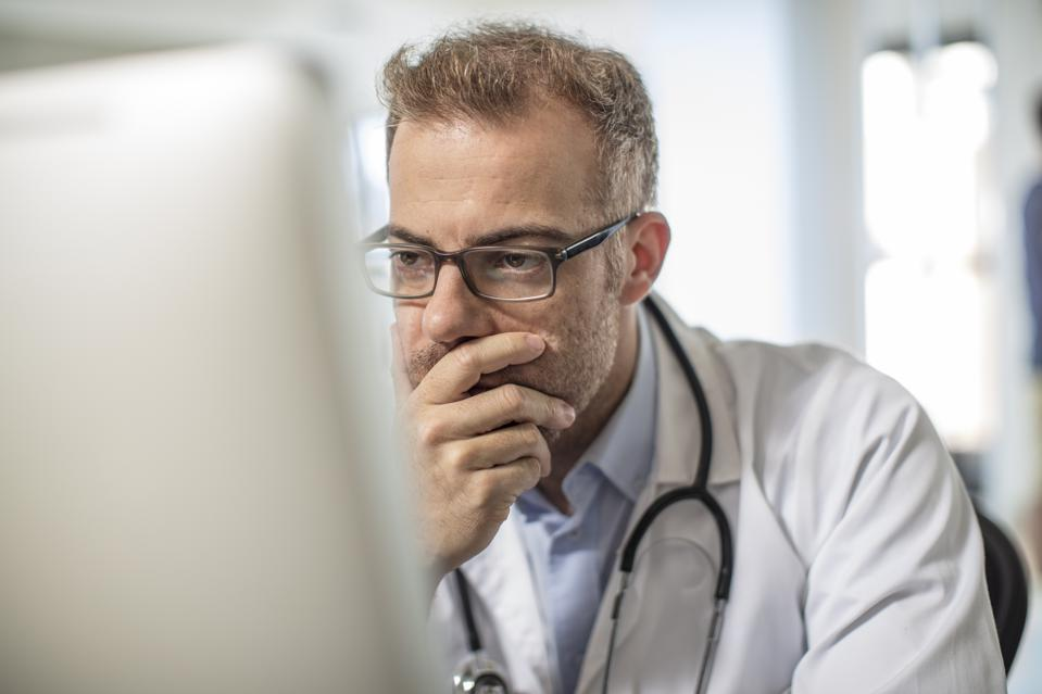 Doctor sitting at desk working on computer