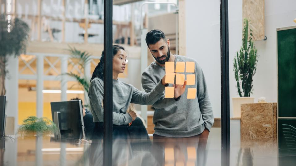 Businessman discussing with businesswoman sticking adhesive notes on glass wall in office