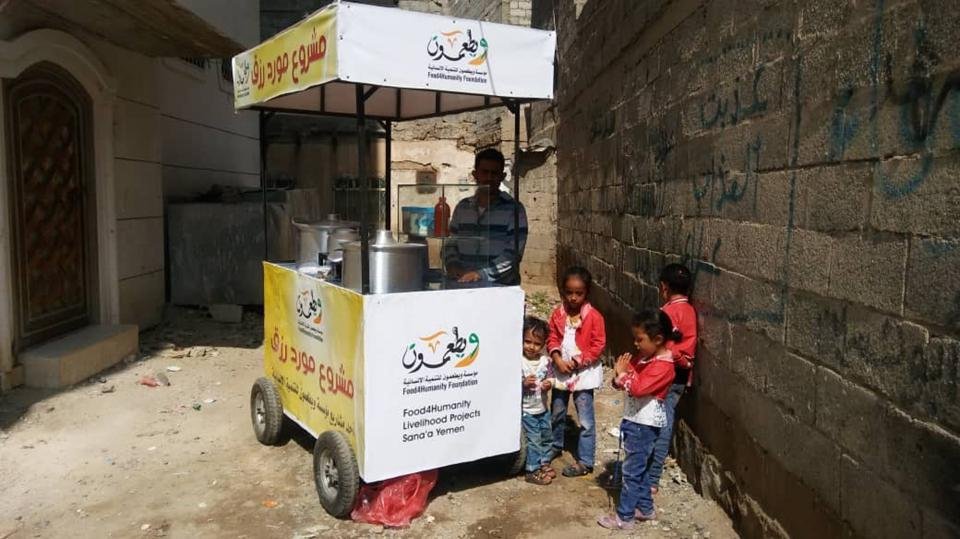 Street vendor supported by Food4Humanity in Yemen with children.