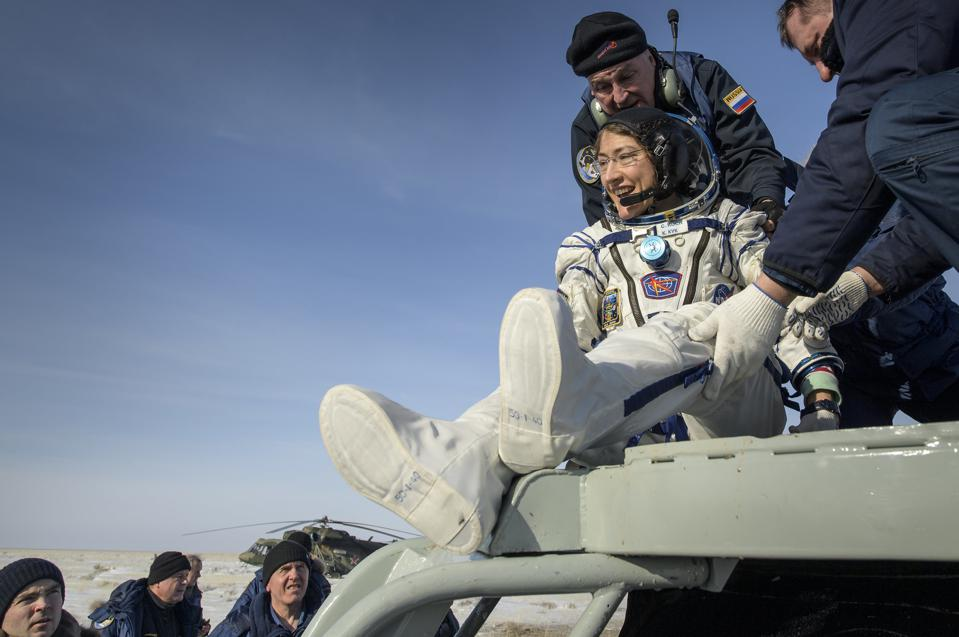 NASA astronaut Christina Koch (in spacesuit) touches down on Earth.
