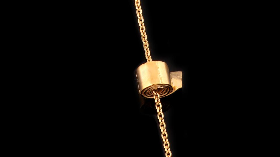 A golden toilet roll on a necklace