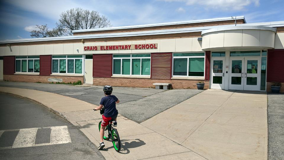 Boy on a bike in front of a building with a sign saying ″Craig Elementary School″