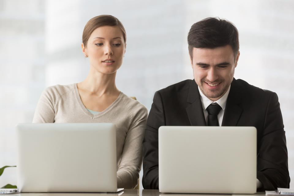 Interested curious businesswoman looking at businessman laptop screen, corporate espionage