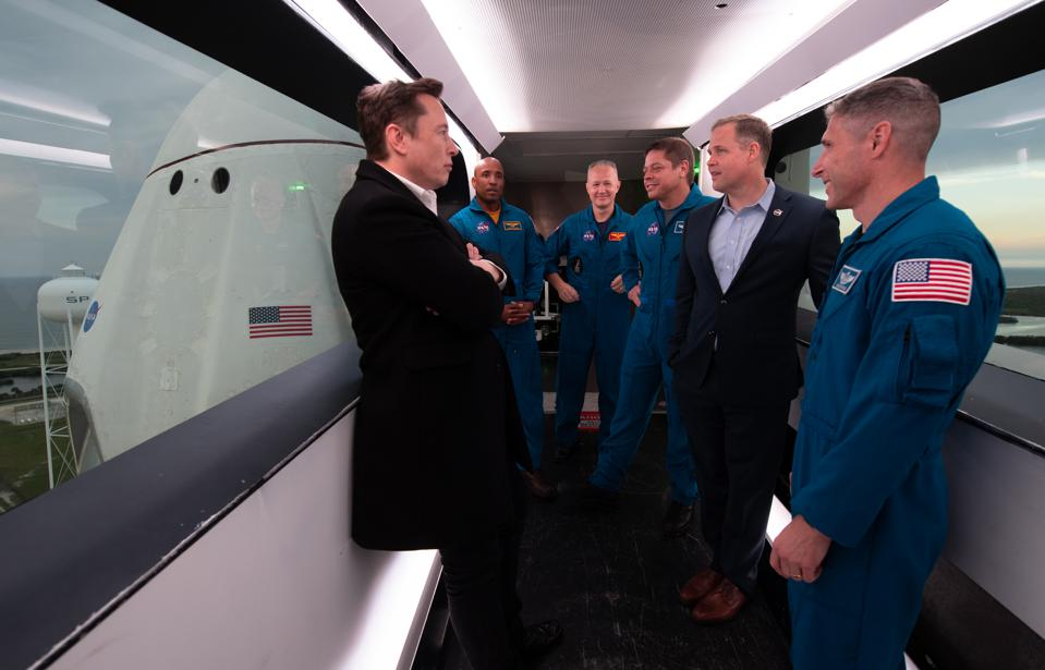 SpaceX CEO and Chief Designer Elon Musk, left, NASA astronauts Victor Glover, Doug Hurley, Bob Behnken, NASA Administrator Jim Bridenstine, and NASA astronaut Mike Hopkins are seen inside the crew access arm with the SpaceX Crew Dragon spacecraft visible behind them during a tour of Launch Complex 39A.