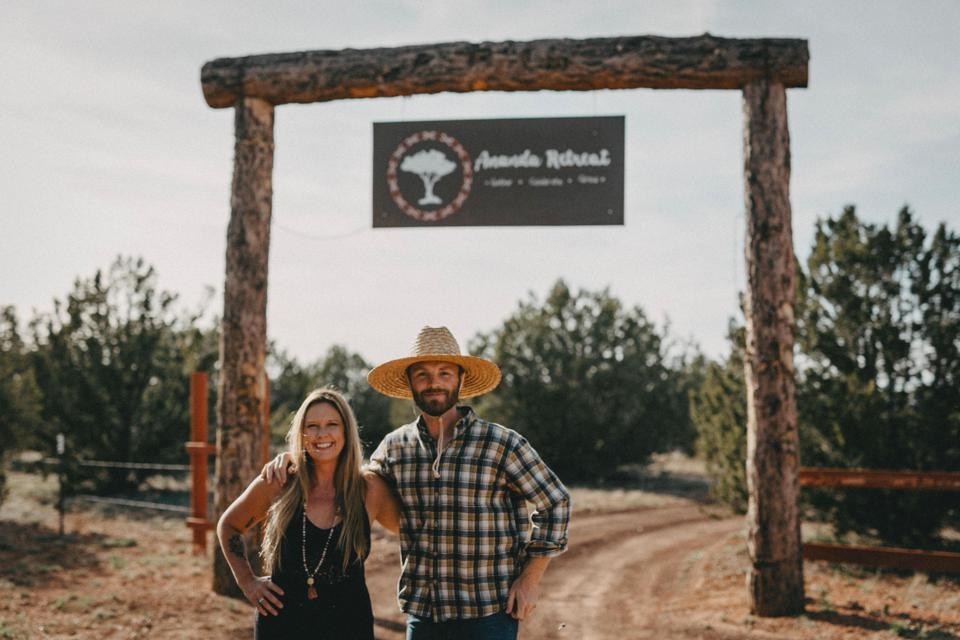 Couple stands in front of sign hanging over entrance in desert