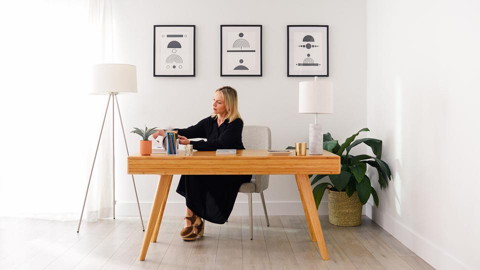 A woman sitting at a wooden desk rented from Fernish, with lamp[, a chair, and wall art, also from Fernish, a furniture subscription rental service.