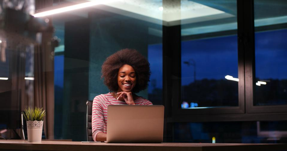 Young, smiling black woman engages with video conference call in a modern home.