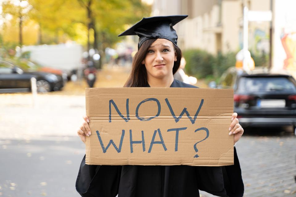 Sad Graduate Student Standing With Now What Placard