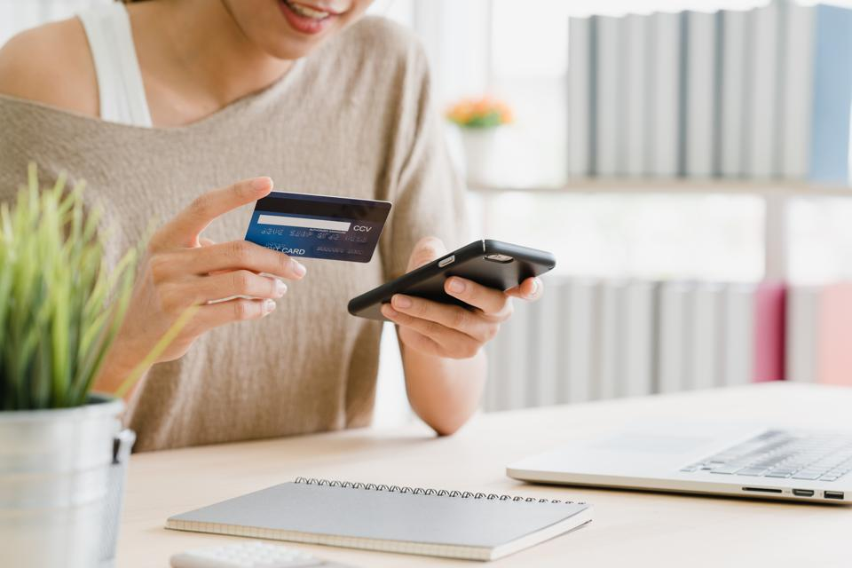 Midsection Of Woman Holding Credit Card While Using Mobile Phone For Online Shopping On Table
